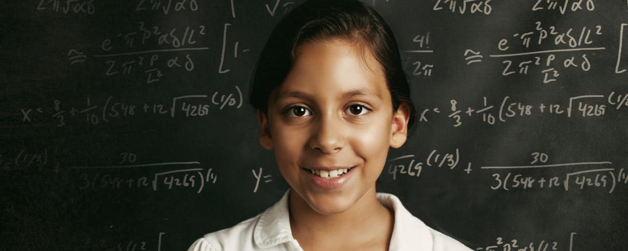 A young student in front of a chalkboard with equations written on it