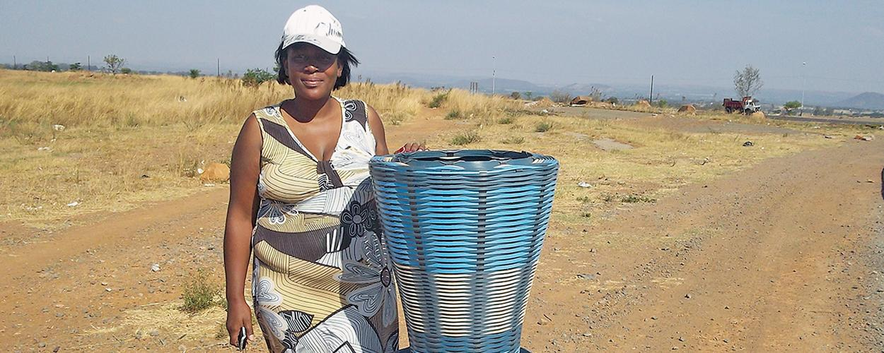 south african woman shows basket while holding cell phone