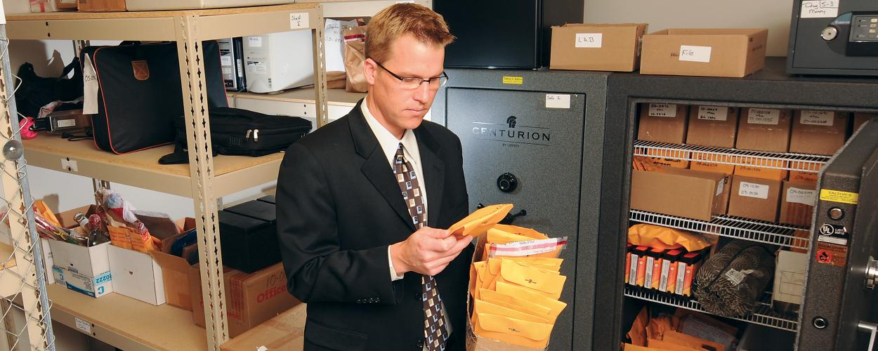 man looking at evidence envelope
