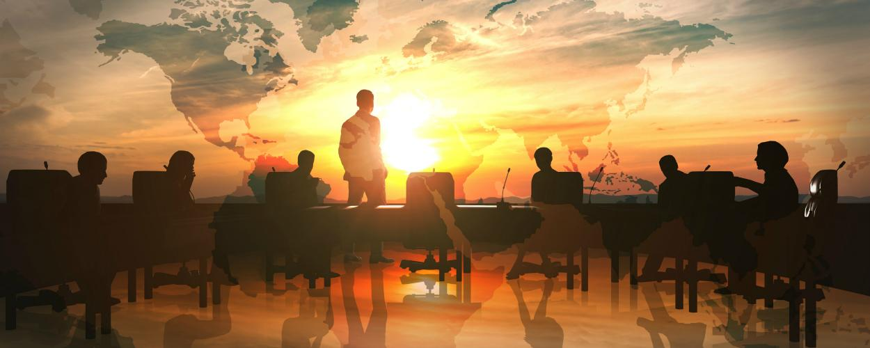 A group of professionals talk while silhouetted in front of a large world map.