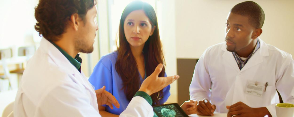 Two male doctors and a female doctor hold a discussion at a conference table.