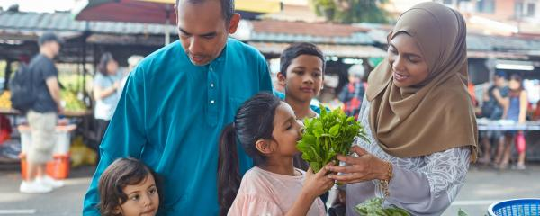 A family buying vegetables at an outdoor market