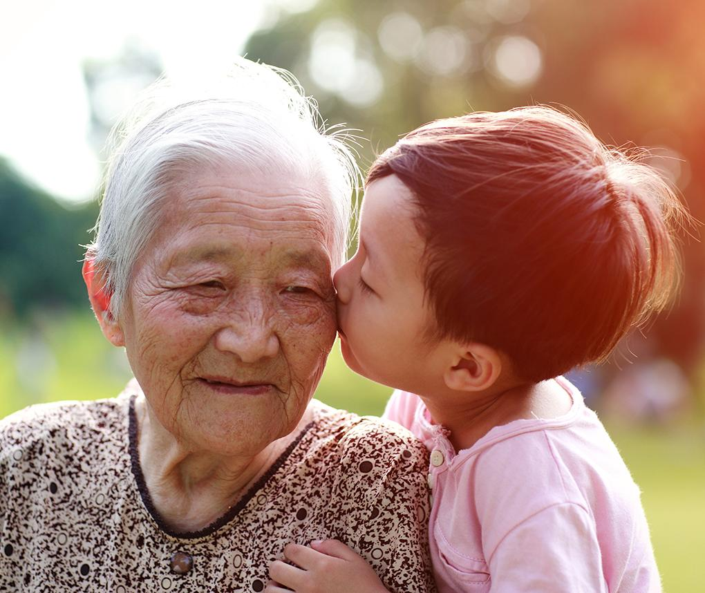 An older Asian woman gets a kiss from her grandchild.