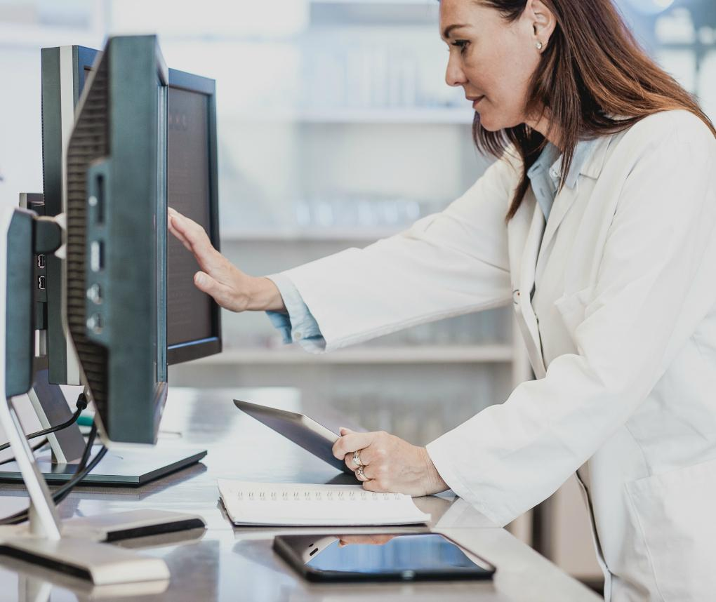A female scientist in a white lab coat works with a touchscreen computer.