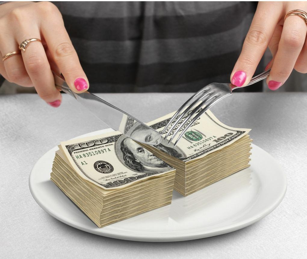 woman's hands cutting money on plate