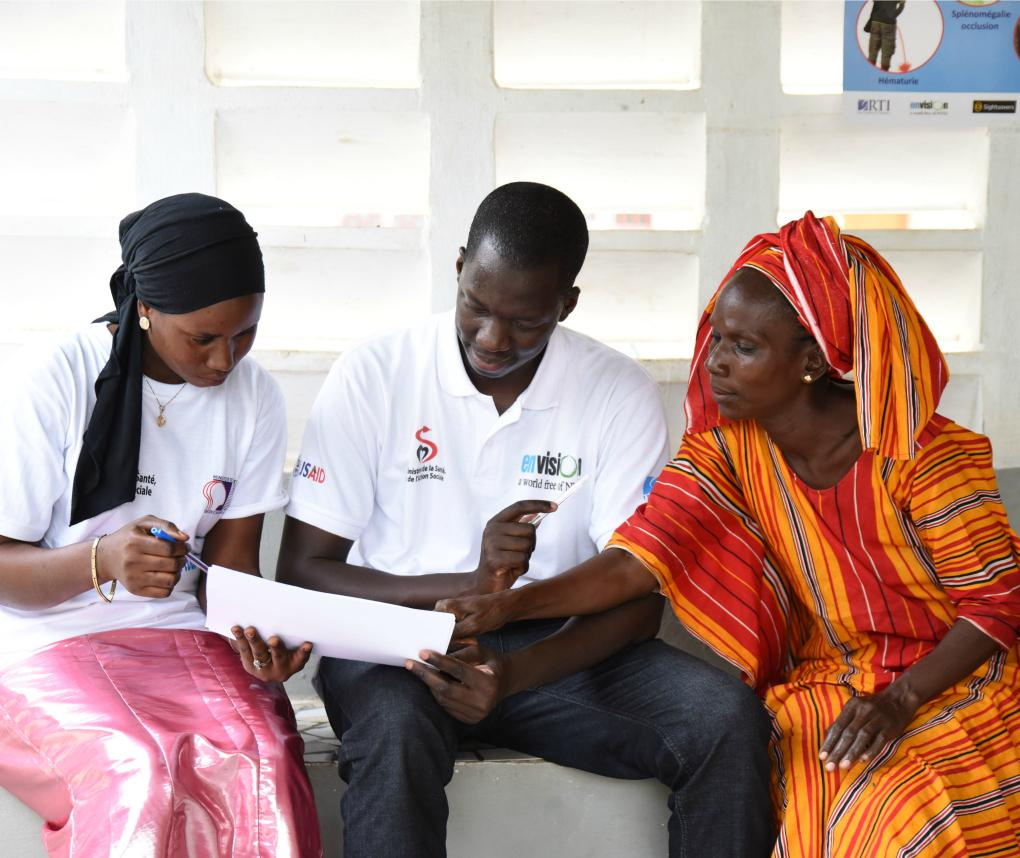 Workers with the ENVISION project, one man and two women, consult a document.
