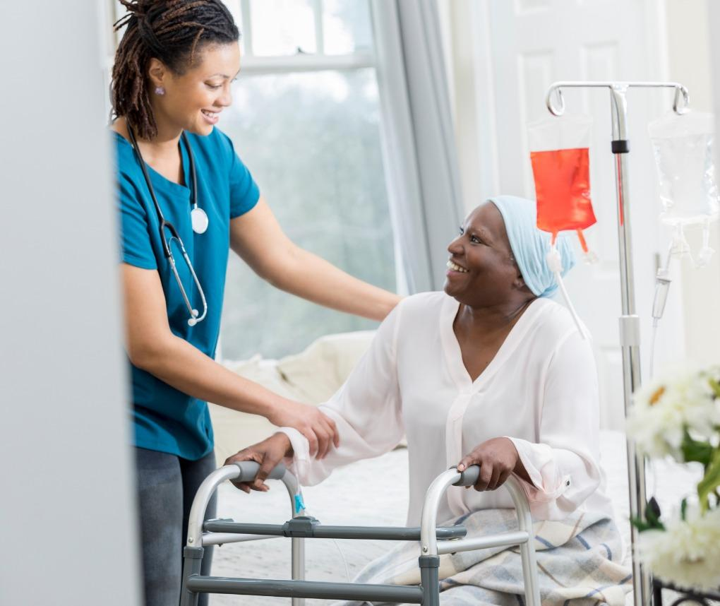 A hospice nurse attends to a female patient