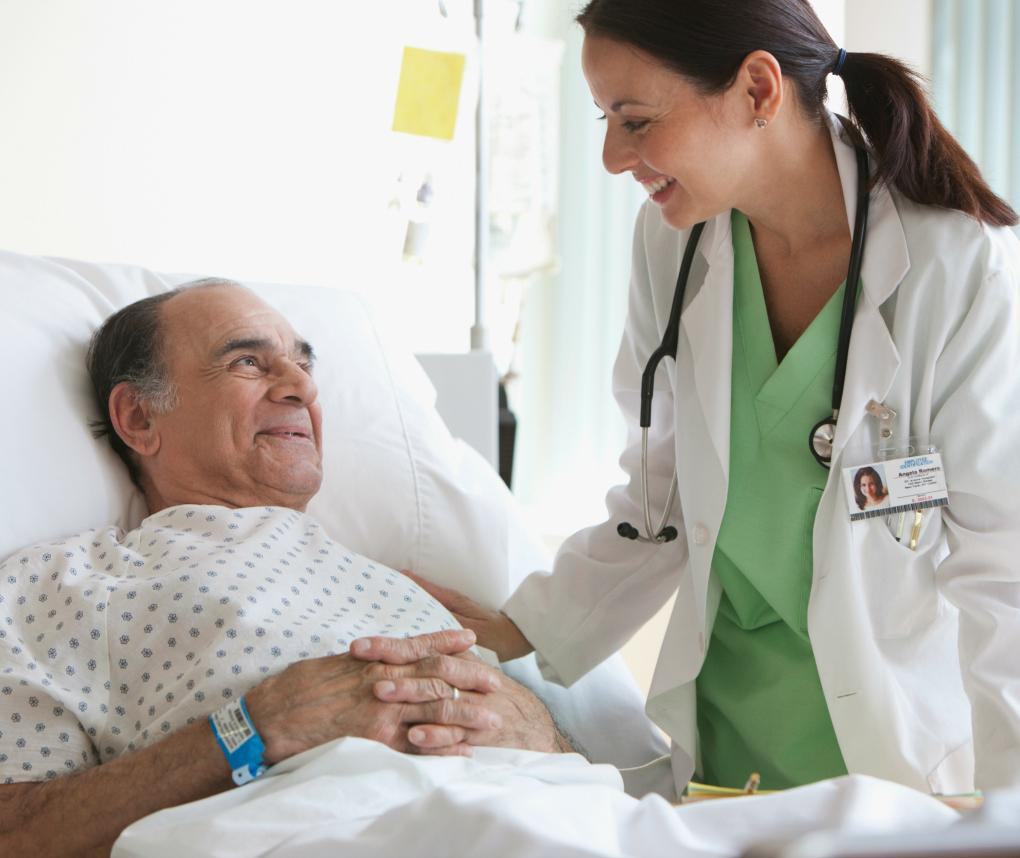 A female doctor stands next to the hospital bed of an older male patient, who is smiling.