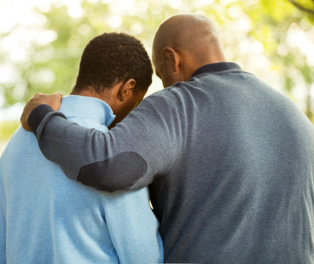 An African-American father places his arm around the shoulders of his adult son.