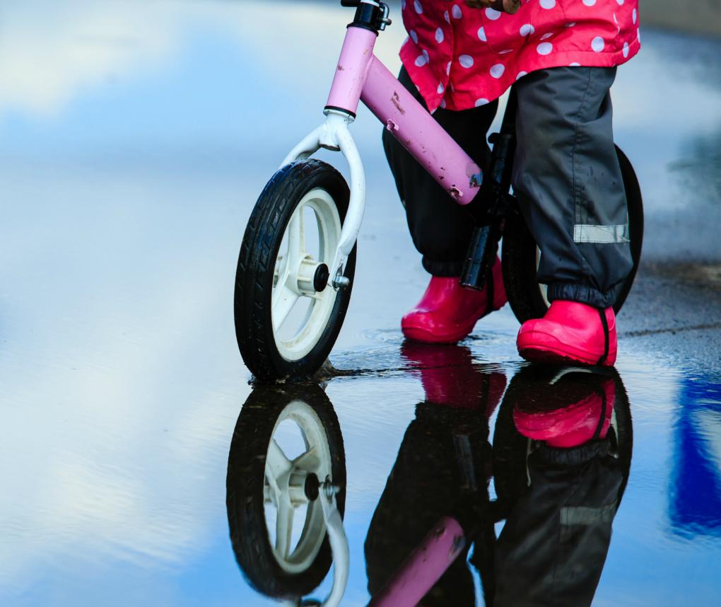 A little girl in a pink raincoat and boots rides a push bike through a puddle.