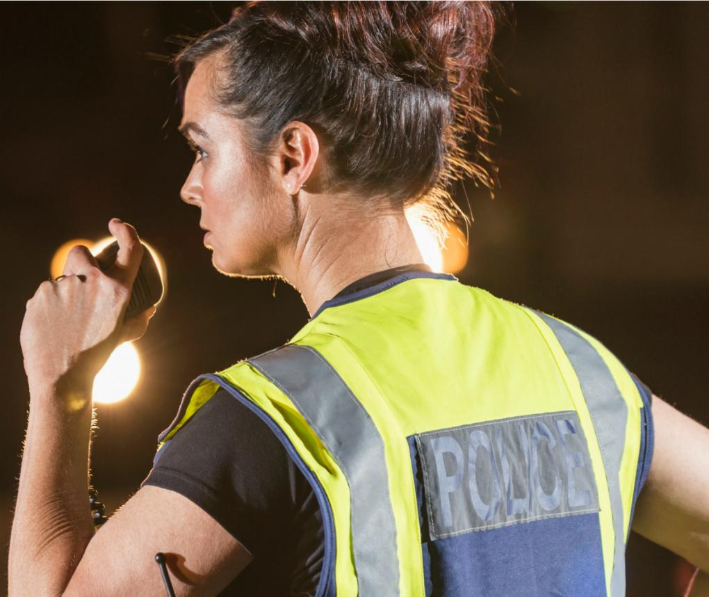 A female police officer talks into a handheld radio while watching traffic on a street at night.