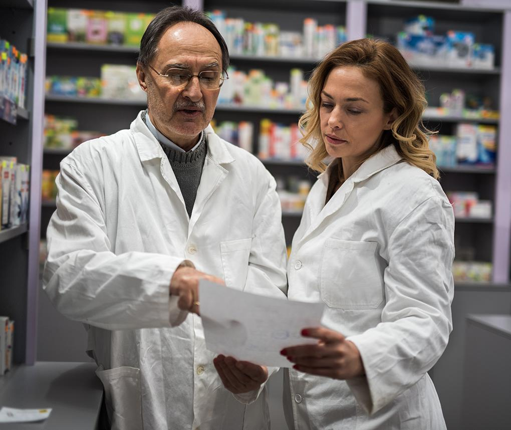 A doctor and pharmacist consult with each other in front of shelves filled with prescription medications.