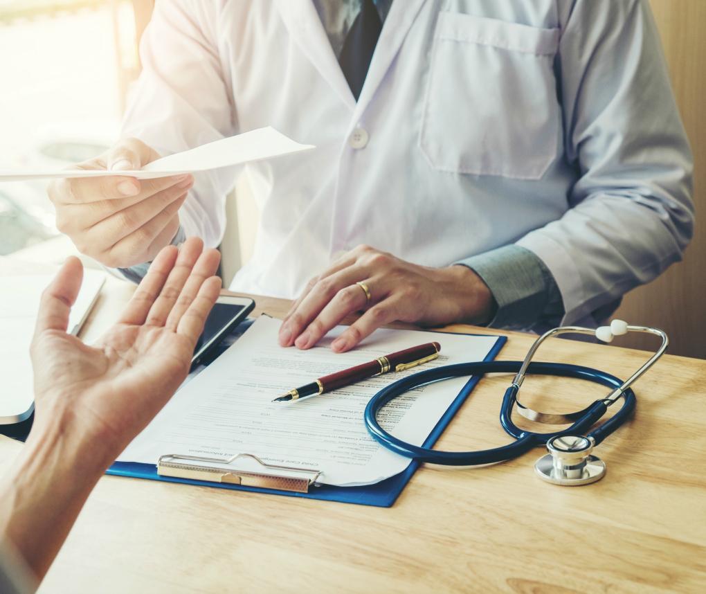 A doctor hands a prescription form to a patient across a desk.