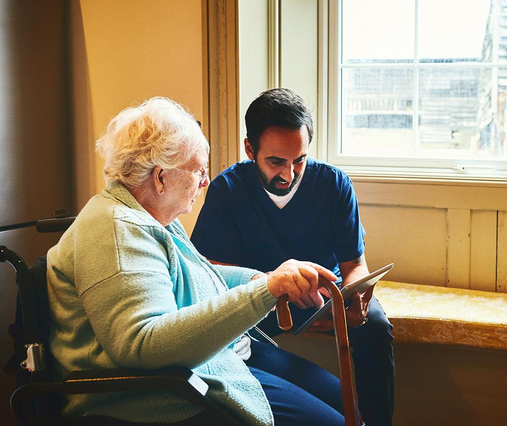 A senior woman and a male caregiver look at photos on a tablet.
