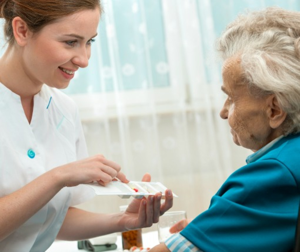 A nurse gives medicine to a woman in a nursing home