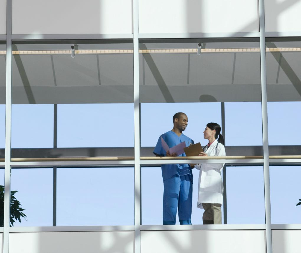 A male and female doctor talk in a glass-walled hospital walkway.