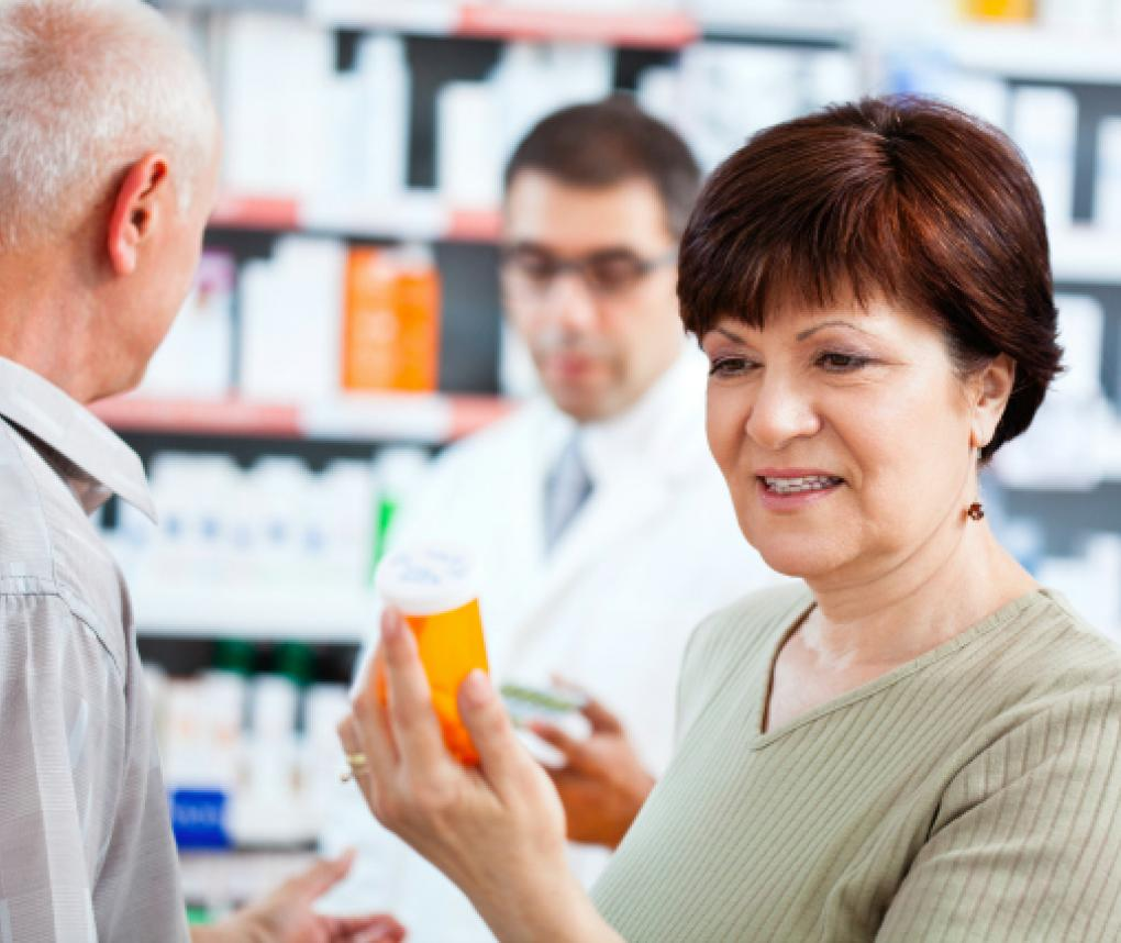Woman reading a pill bottle in a pharmacy
