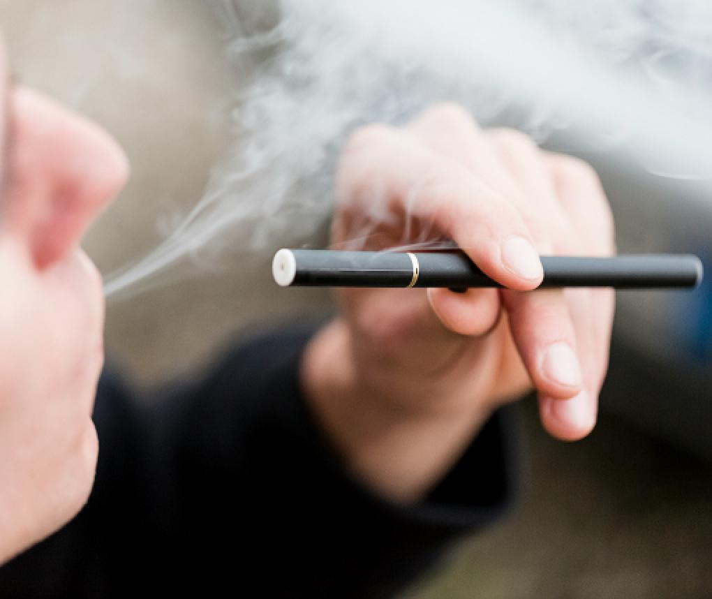 A teenage boy uses an electronic cigarette