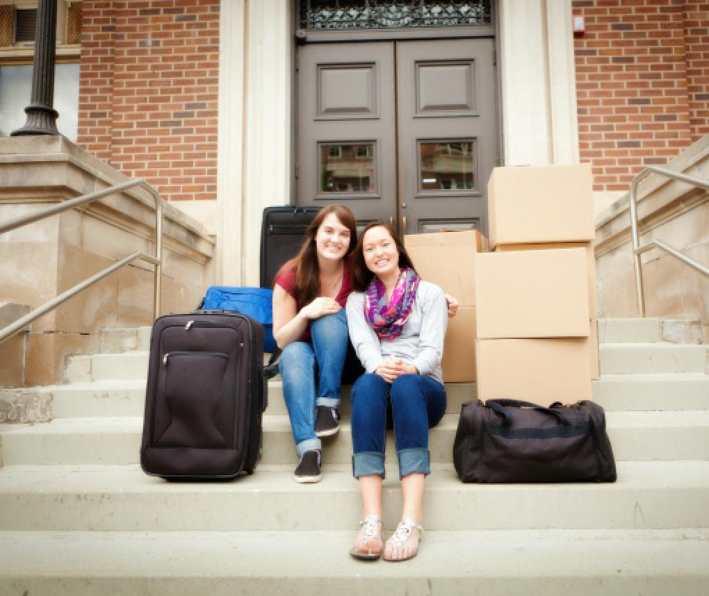 Two young women sit with packages on the steps of a building