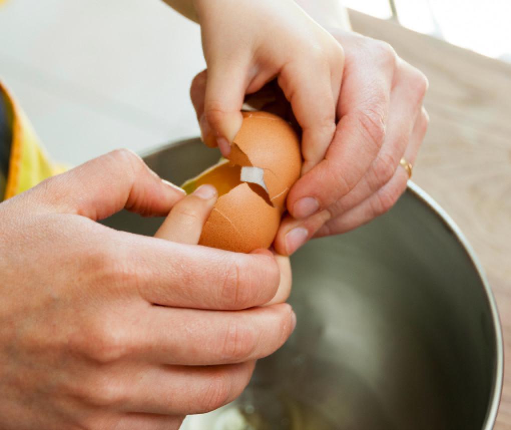 A person cracks an egg into a bowl