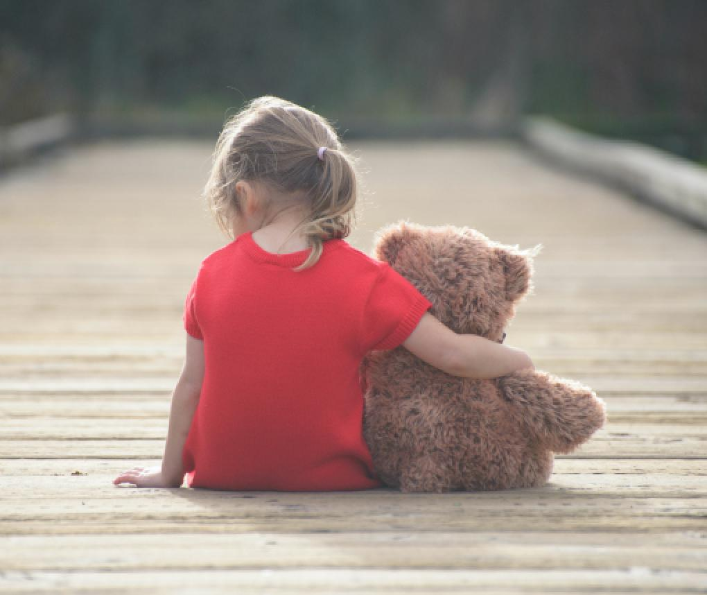 girl sitting outside with teddy bear