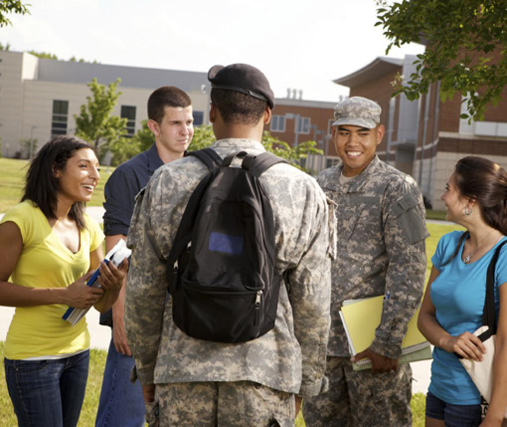 Two students in military uniforms talk with other students on a college campus.
