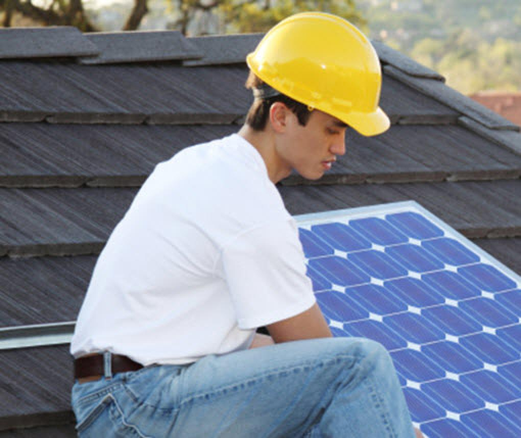 worker installs a solar panel on a roof