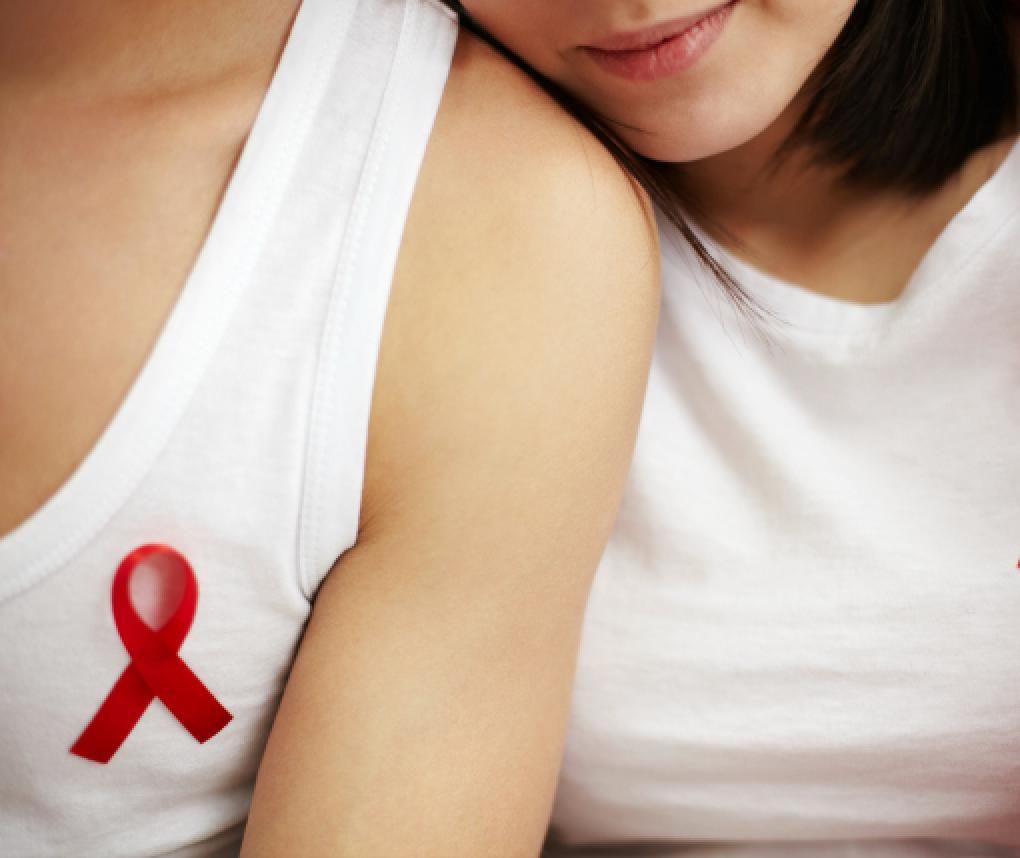 Two women wearing HIV awareness ribbons