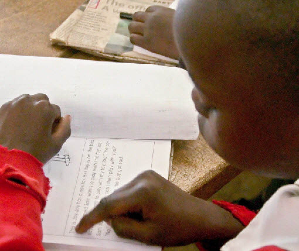 child reading in a classroom in Kenya