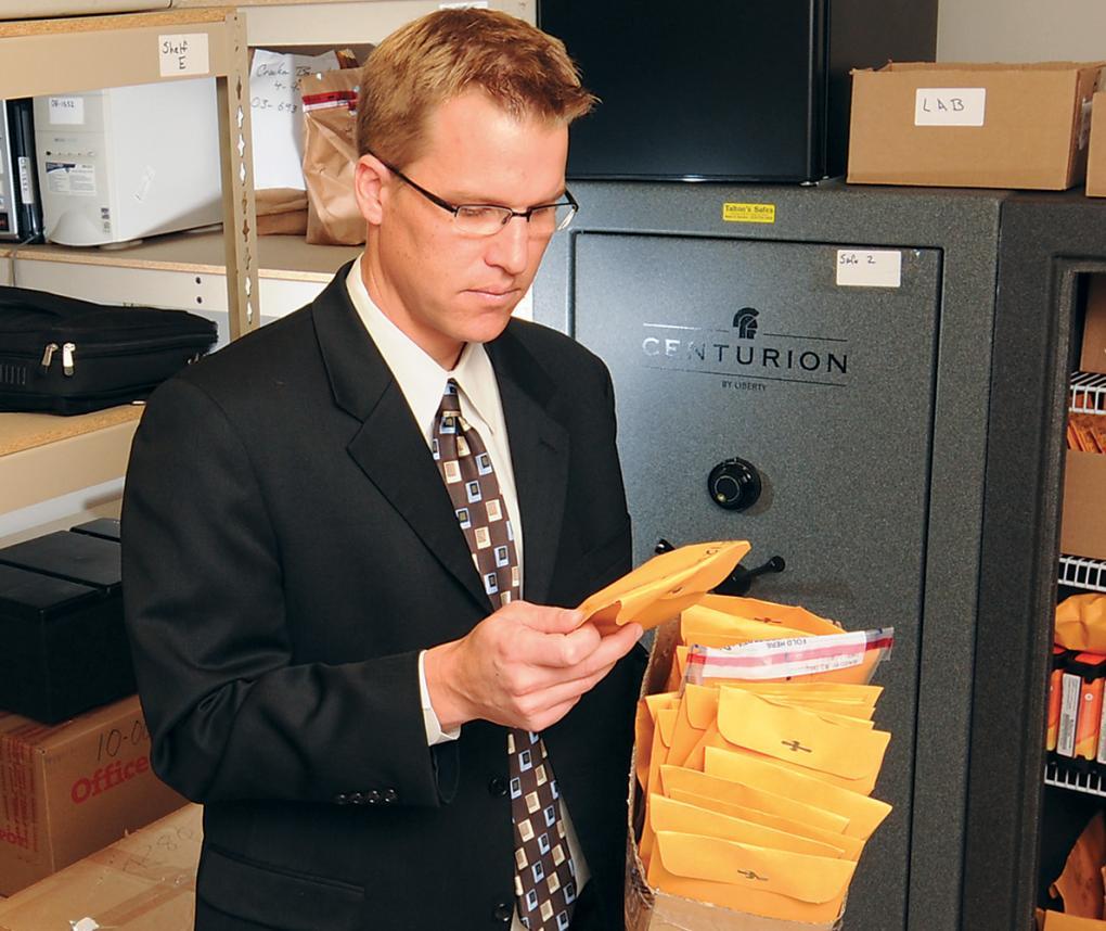 man looking at evidence envelope
